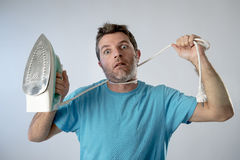 Young crazy desperate and frustrated man doing housework holding Stock Images