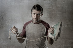 Young crazy desperate and frustrated man doing housework holding iron and cable stressed Stock Image
