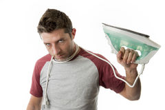Young crazy desperate and frustrated man doing housework holding Stock Photography
