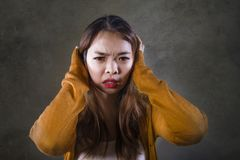 Sad and desperate Asian Korean woman holding her head depressed feeling anguish and pain on isolated dark background in pain face. Young crazy desperate and sad stock photo