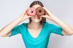 Young crazy girl bite one lips in blue blouse standing, holding, covering eyes with pink and chocolate donuts,looking through don. Uts like making glasses on royalty free stock photo
