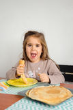 Young crazy girl eating a stack of pancakes. Royalty Free Stock Image