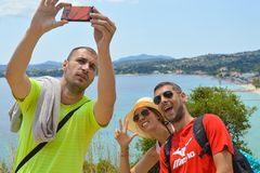 Young crazy group of friends with modern mobile smart phone maki. Ng a selfie.Happy people with taking picture with smartphone in summer at seaside. Youth royalty free stock image
