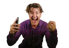 Young crazy happy and excited man celebrating success making money online gambling with mobile phone winning internet bet isolated. Natural portrait of young stock photography