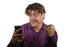 Young crazy happy and excited man celebrating success making money online gambling with mobile phone winning internet bet isolated. Natural portrait of young royalty free stock image