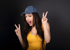 Young crazy happy female model in blue hat showing victory gestu. Re on grey dark background with empty copy space Royalty Free Stock Photo