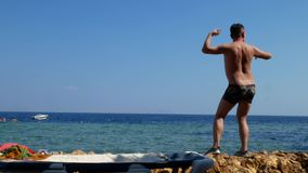 Young crazy man dancing. On beach with marine sea surface background stock video