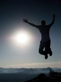 Young crazy man is jumping on rock. Silhouette of jumping man Stock Images