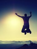 Young crazy man is jumping on rock. Silhouette of jumping man Royalty Free Stock Images