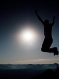 Young crazy man is jumping on rock. Silhouette of jumping man Stock Photo