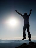 Young crazy man is jumping on rock. Silhouette of jumping man Stock Photography