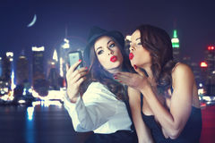 Young crazy girlfriends taking selfie at night in city. Sending kisses royalty free stock image