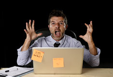 Young crazy stressed businessman screaming desperate working in stress with laptop computer. Heavy work load isolated on office desk black background in stock photo