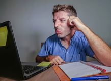 Young crazy stressed and upset man working messy at office desk desperate gesturing mad to laptop computer angry and frustrated in Stock Photo