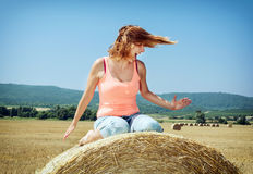 Young crazy woman sits on the stack of straw and throws with her Royalty Free Stock Image