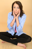Young Crazy Woman Sitting on the Floor Pulling Silly Facial Expression Royalty Free Stock Photo