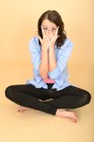 Young Crazy Woman Sitting on the Floor Pulling Silly Facial Expression Royalty Free Stock Images