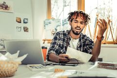 Young creative artist feeling fed up while working all day long. Fed up. Young creative artist with dreadlocks feeling fed up while working all day long stock photography