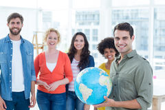 Young creative business people with a globe Royalty Free Stock Photos