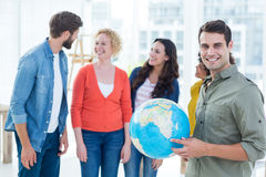 Young creative business people with a globe Stock Photography