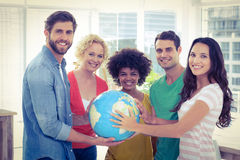 Young creative business people with a globe Stock Photos