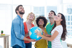Young creative business people with a globe Royalty Free Stock Image