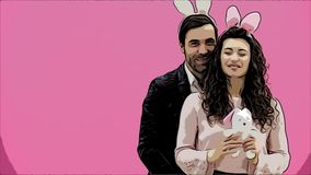 Young creative couple on pink background. With bunny ears on the head. For this, the wife holds a soft toy-hare, a man. Shows a class. Give a sincere smile stock footage