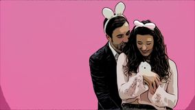 Young creative couple on pink background. With hackneyed ears on the head. During this man gives a soft toy with a hare. To his wife. Embracing a girl looking stock video