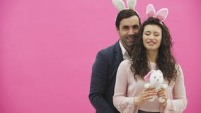 Young creative couple on pink background. With hackneyed ears on the head. During this, a wife holds a soft toy hare, a. Man shows a class. Giving a genuine stock footage