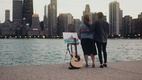 Young creative couple on the shore of Michigan lake, Chicago, America. Woman drawing, man holding the guitar in evening stock video footage