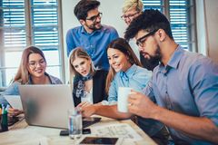 Young creative coworkers working with new startup project. In office stock image