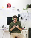 Young creative designer man at phone working at office and listening music. Stock Image