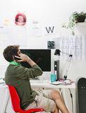 Young creative designer man at phone working at office. Stock Image