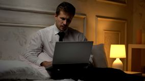 Young creative director working on project late at night in hotel, business trip royalty free stock photography