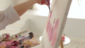 A creative girl draws flowers on a white canvas in the drawing Studio. Close-up. A young creative girl draws flowers on a white canvas in the drawing Studio stock video footage