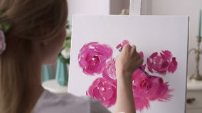 A young creative girl draws flowers on a white canvas in the drawing studio. Art. Beautiful women are creating art. Young artist painting in the house stock video