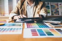 Young creative Graphic designer using graphics tablet to choosing Color swatch samples chart for selection coloring with work too. Ls and accessories at stock images