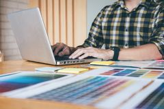 Young creative Graphic designer using graphics tablet to choosing Color swatch samples chart for selection coloring with work too royalty free stock photography