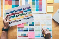 Young creative Graphic designer using graphics tablet to choosing Color swatch samples chart for selection coloring with work too. Ls and accessories at stock image