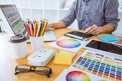 Young creative graphic designer working on project architectural drawing and color swatches, selection coloring on graphic chart royalty free stock photo