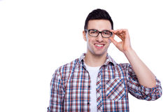 Young and creative. Handsome young man adjusting his eyewear and smiling while standing against white isolated background Stock Images