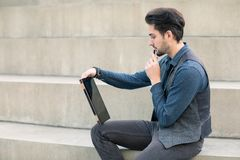 Young creative man sitting on the stairs with a modern tablet wi. Th a stylus pen in his hand Royalty Free Stock Photo