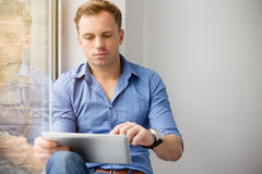 Young creative man sitting at window and using tablet computer Stock Images