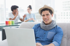 Young creative man using laptop on couch stock photo