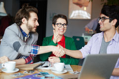 Young Creative People Making a Bet. Portrait of three creative people wearing casual clothes during meeting at table, two smiling friends shaking hands making a Royalty Free Stock Photography