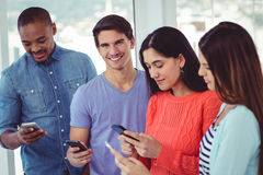 Young Creative Team Looking At Phones Stock Image