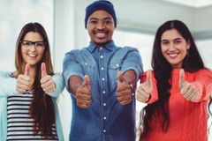 Young creative team showing thumbs up Royalty Free Stock Images