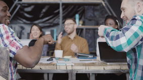 Young creative team working at modern office. Mixed race group business meeting. African and caucasian man fist greeting. Young creative team working at modern stock video