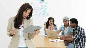 Young creative team working together with woman using tablet. In creative office stock footage