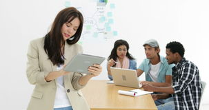 Young creative team working together with woman using tablet. In creative office stock video footage